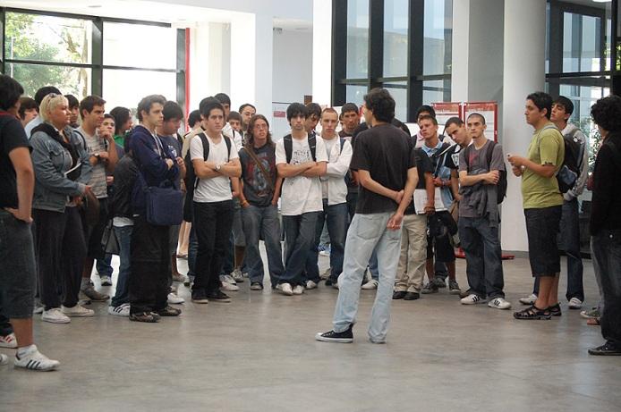 Imagen alumno exponiendo rodeado de otros alumnos escuchando la exposición